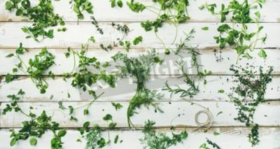 Papiers peints Plat-lay de diverses herbes vertes fraîches. Persil, menthe, aneth, coriandre, romarin, thym sur fond en bois blanc rustique, vue de dessus, composition large. Concept de cuisine végétalienne saine