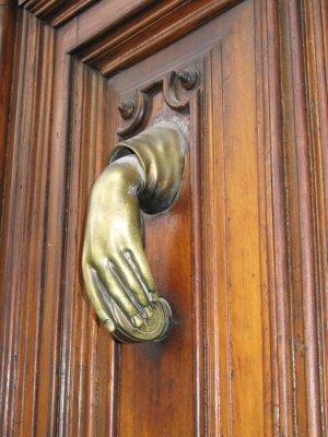 Porte heurtoir main ancienne dans une main féminine, sur la vieille porte wodden.