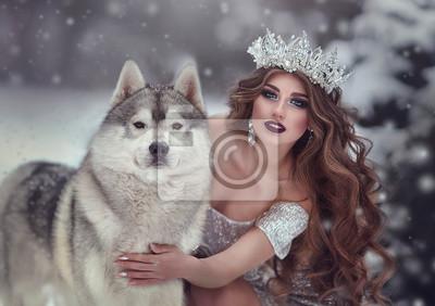 Papiers peints Portrait de femme en robe d'argent et couronne en forme de reine des neiges, en forêt d'hiver avec un chien Husky. La fée princesse et le loup en hiver.