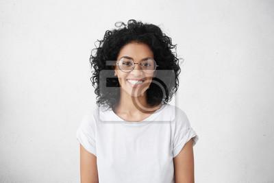 Papiers peints Portrait intérieur d'une belle jeune femme brune à peau sombre avec une coiffure hirsute souriante, montrant ses dents blanches à la caméra tout en se sentant heureuse et insouciante sur son premier j