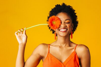 Papiers peints Portrait of a happy young woman holding orange Gerbera daisy covering her eye with eyes closed