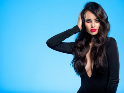 Papiers peints Portrait of beautiful young woman with bright blue makeup.  Pretty girl with long black hair. Brunette woman in a black clothes. Sexy girl. Beautiful brunette with bright red lipstick on her lips..