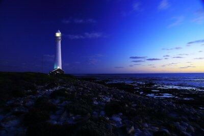 Papiers peints Pour le phare / Une vue du soir du phare de Slangkop avec des rochers et des nuages