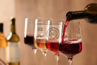 Papiers peints Pouring wine from bottle into glass on blurred background, closeup