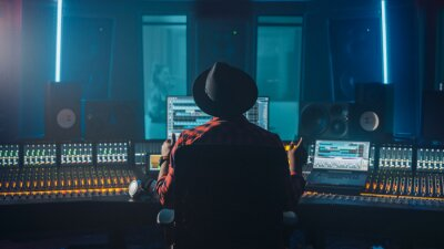 Papiers peints Producer, Audio Engineer Uses Control Desk for Recording New Album Track in Music Record Studio, in the Soundproof Room Musician, Artist, Performer Sings a Song from New Album. Back View