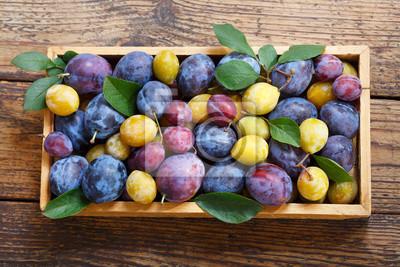 prunes colorées avec des feuilles dans une boîte en bois