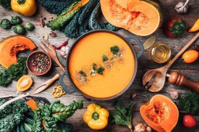 Papiers peints Pumpkin soup with vegetarian cooking ingredients, wooden spoons, kitchen utensils on wooden background. Top view. Vegan diet. Autumn harvest. Healthy, clean food and eating concept. Zero waste
