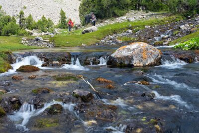 Papiers peints Rapid and wide cascade river Fast moving water vivid rocky stones and group of people walking on green meadow on background