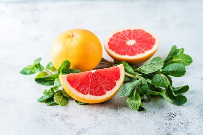 Red grapefruit with slaces and mint leaves on a light background