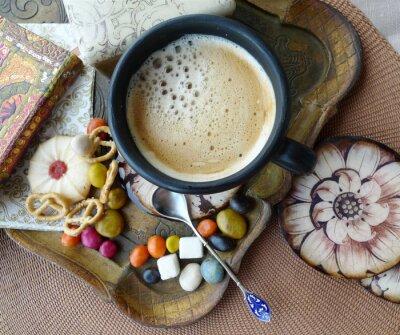 Rétro vie toujours. Une tasse de café avec de la crème, des biscuits et des bonbons sur un plateau.