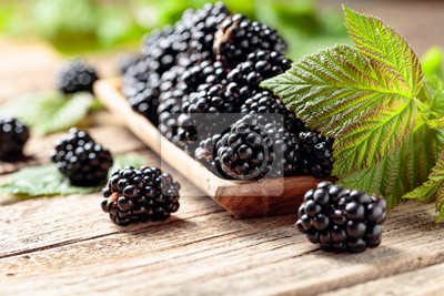 Ripe juicy blackberries with leaves on a wooden table.