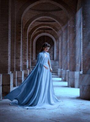 Papiers peints Sad Snow Queen walks in old castle. blue silk long raincoat train flying motion. Elven hairstyle cute face. Vintage fantasy art retro style. Frozen Fabulous woman photo shoot. sun magic shine rays