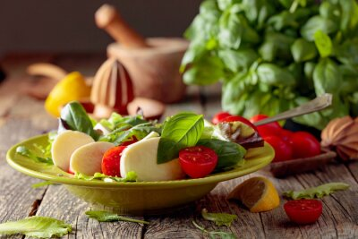 Salad with mozzarella, tomato and basil in green plate on a old wooden background.