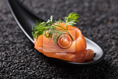Salted salmon with dill on the background of black sesame.