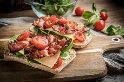 Sandwich Ciabatta avec salade de roquette, bacon et fromage jaune.