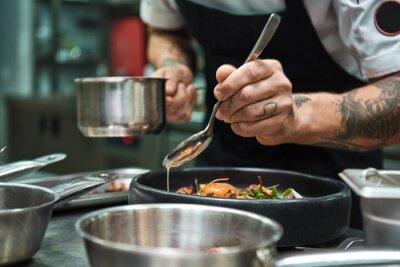 Papiers peints Secret recipe. Close up photo of chef hands with several tattoos adding a sauce to italian pasta Carbonara.