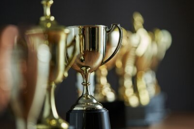 Papiers peints selective focus row of trophy on the wooden table against dark gray background