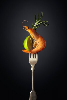 Shrimp with rosemary and lime on a black background.