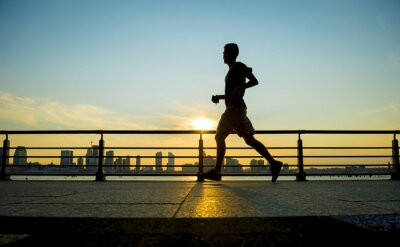 Papiers peints Silhouette de joggeurs courir au coucher du soleil en face de l'horizon de la ville