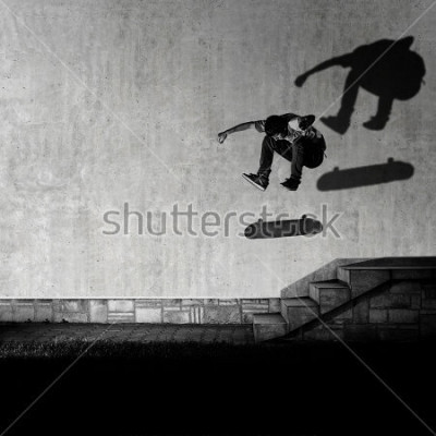 Papiers peints Skater making 360 flip trick from 4 stairs - artistic motion blur shot in black and white color tone.