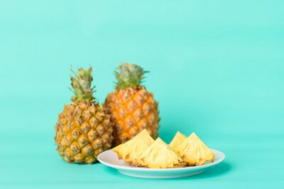 Sliced pineapple fruit on plate with pastel green background, Tropical fruit
