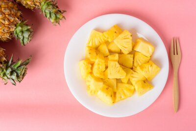 Sliced pineapple fruit on white plate with fork ready to eating on pastel pink background, Tropical fruit