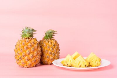 Sliced pineapple fruit on white plate with pastel pink background, Tropical fruit
