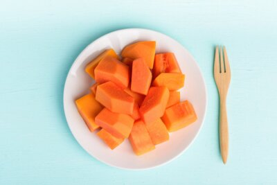 Sliced ripe papaya fruit on plate and fork on pastel color background, Tropical fruit