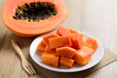 Sliced ripe papaya fruit on white plate with fork ready to eating on wooden background, Tropical fruit