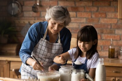 Papiers peints Smiling mature Hispanic granny and small granddaughter work with flour bake cookies in kitchen at home. Happy caring senior grandmother and little grandchild cook breakfast or dessert together.