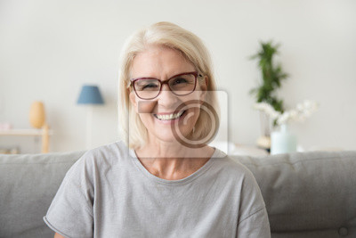 Papiers peints Smiling middle aged mature grey haired woman looking at camera, happy old lady in glasses posing at home indoor, positive single senior retired female sitting on sofa in living room headshot portrait