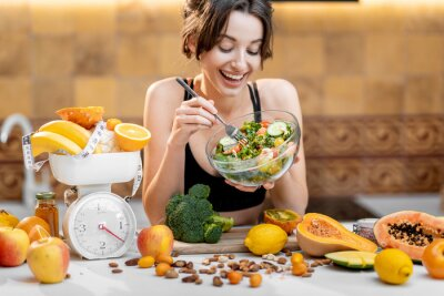 Papiers peints Sports woman eating salad, standing with lots of healthy fresh food on the kitchen. Concept of losing weight, sports and healthy eating