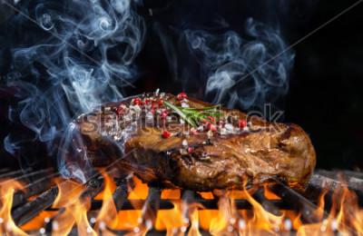 Papiers peints Steak de bœuf sur le grill avec feu noir