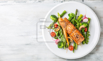 Papiers peints Steak de saumon grillé avec asparagos brocoli carotte tomates radis haricots verts et petits pois. Farine de poisson avec des légumes frais