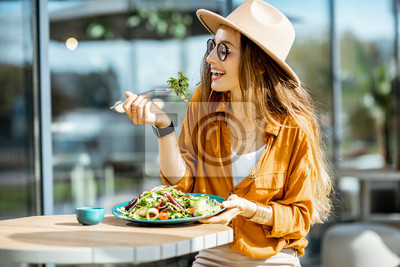 Papiers peints Stylish young woman eating healthy salad on a restaurant terrace, feeling happy on a summer day