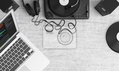 Sur un bureau une ordinateur portable une platine un casque papier