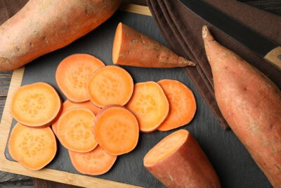 Papiers peints Sweet potato, board and towel on wooden background, top view