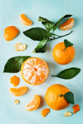 Tangerine fruit with slices, peel and leaves