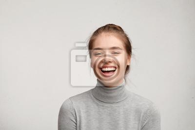 Papiers peints Tête de la bonne femme chanceuse avec les cheveux attachés peau pure et large sourire heureux de regarder à la caméra. Femme sincère avec belle apparence portant des vêtements décontractés isolés sur