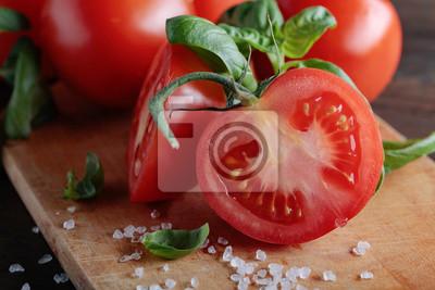 Tomates rouges au basilic vert sur une table en bois.