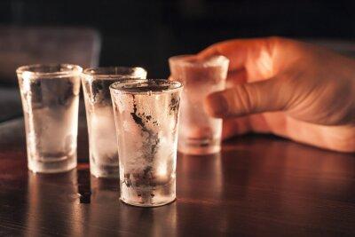 Papiers peints Tourné verre de vodka à la main sur une table en bois.