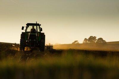 Papiers peints Tracteur dans le coucher du soleil labourant le terrain