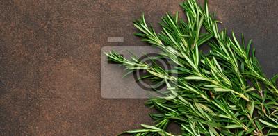 Papiers peints Un bouquet de romarin frais sur un fond de béton brun. Fond de nourriture biologique.