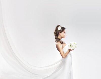Papiers peints Un jeune mariée caucasienne posant dans une robe blanche avec des fleurs