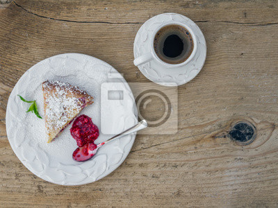 Un morceau de gâteau au fromage aux framboises et une tasse de café sur un bois