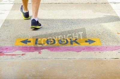 Un regard noir et jaune plâtré deux façons signe sur la route, avec les yeux tirés à l'intérieur du o, qui met en garde les piétons de faire attention de voitures et de vélos à un passage pour piétons