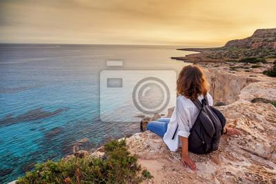Papiers peints Un voyageur de la jeune femme élégante regarde un beau coucher de soleil sur les rochers sur la plage, Chypre, Cap Greco, une destination populaire pour les voyages d'été en Europe
