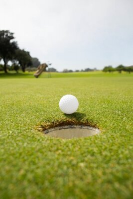 Papiers peints Une balle de golf sur le bord du trou