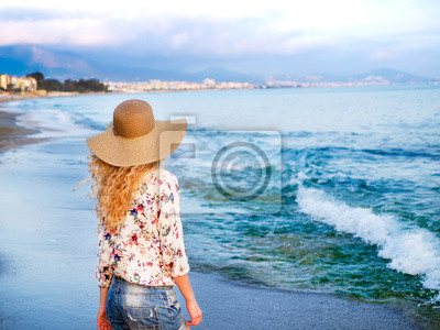 Une fille dans un chapeau sur la côte de la mer