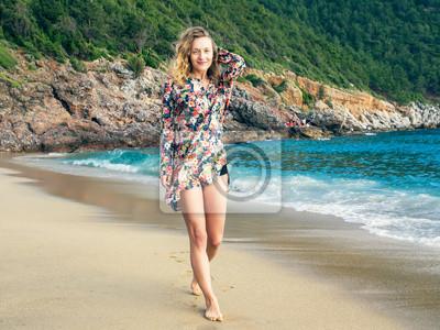 Une jeune fille marche le long de la plage